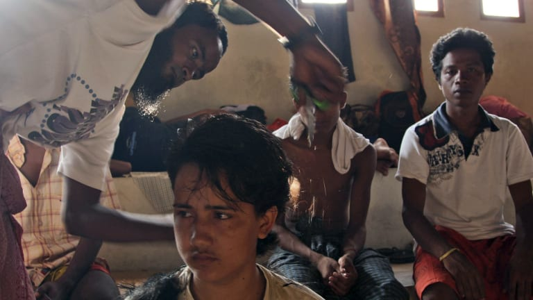 A migrant helps cut his friend's hair at a sports stadium that was turned into a temporary shelter in Lhoksukon, Aceh province, Indonesia on Tuesday.