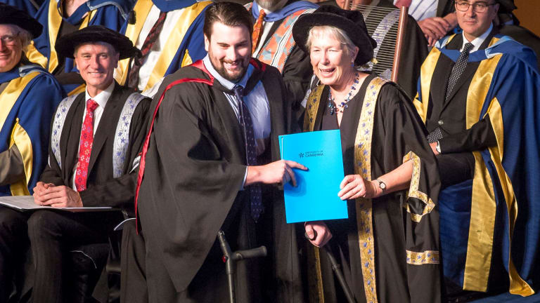 Canberra man and paraplegic Paul Jenkins accepts his degree from University of Canberra Deputy Chancellor Dr Sarah Ryan.