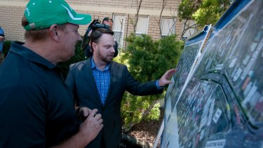 """Deputy mayor Adrian Schrinner and Bicycle Queensland's Andrew Demack look over the plans for the cycling """"superhighway"""" at Woolloongabba."""