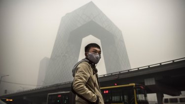 A Chinese man wears a mask as he waits to cross the road near the CCTV building during heavy smog in 2014.
