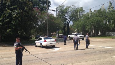Baton Rouge police officers patrol a road block in Baton Rouge after colleagues were shot on Sunday.