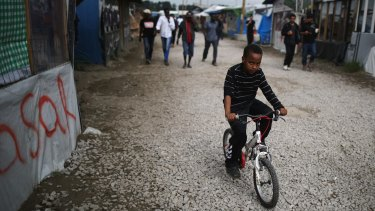 A young boy rides a bicycle in the 'Jungle' migrant camp in Calais.