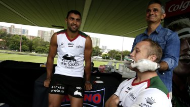 Ready to roll: South Sydney winger Alex Johnston watches as teammate Jason Clarke is fitted for a mouthguard.