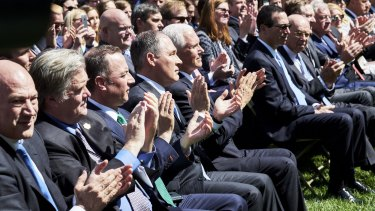 Members of Trump's cabinet applaud as Trump announces his decision on the climate accord.