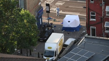 A police forensics officer examines the scene at Finsbury Park, where one person was killed and eight were injured in a van attack.