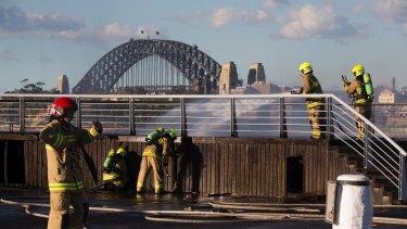 Firefighters extinguish a blaze under a boardwalk next to Jones Bay Wharf in Sydney.