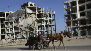 A Palestinian family rides a horse cart as they pass apartment buildings that were destroyed in the most recent Israel-Hamas war, in Gaza Strip.