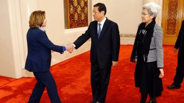 US House Minority Leader Nancy Pelosi, left, shakes hands with Zhang Ping, vice-chairman of China's National People's Congress, in Beijing. At right is Fu Ying.