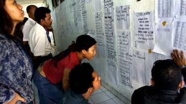 Balinese scan lists of names lining the walls of the Sanglah hospital in Denpasar on October 14, 2002.