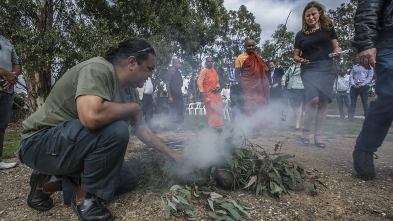 Ranger Adrian Brown conducts the smoking ceremony in Kambah as Housing Minister Yvette Berry walks past.