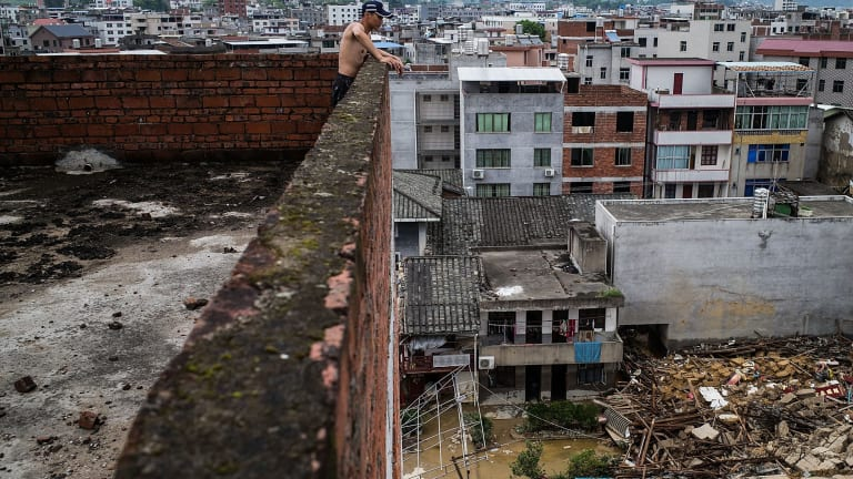 A man looks down at the damage in Fuijan, China.