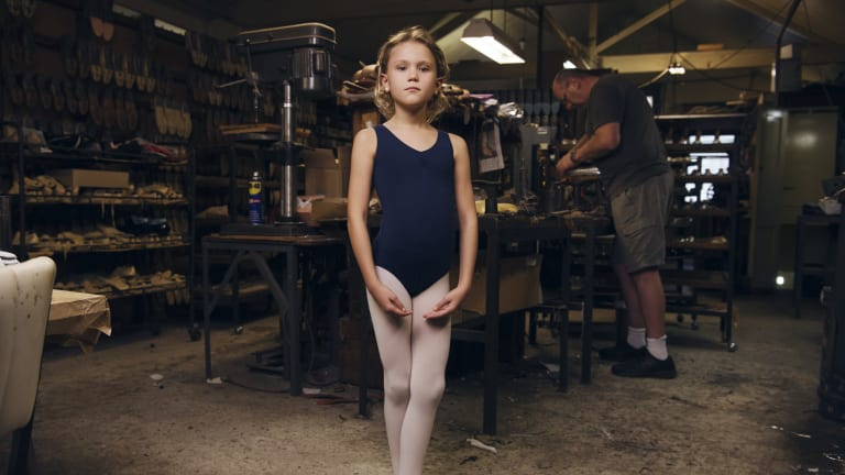 Eight-year-old Alexandra Shaw  in the factory behind Salvios Dancing Shoes, in Randwick, with Phil Salvio toiling in the background.
