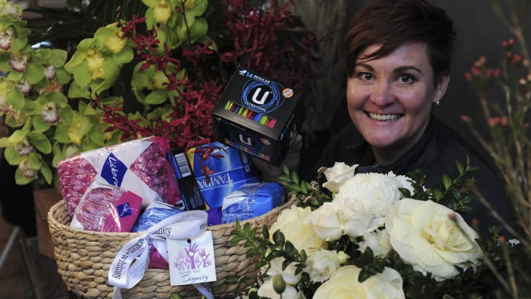 Moxom and Whitney florist on Lonsdale Street, Braddon. Co- owner, Belinda Whitney with a donation basket full of women's sanitary products, donated by customers for the Share the Dignity campaign.