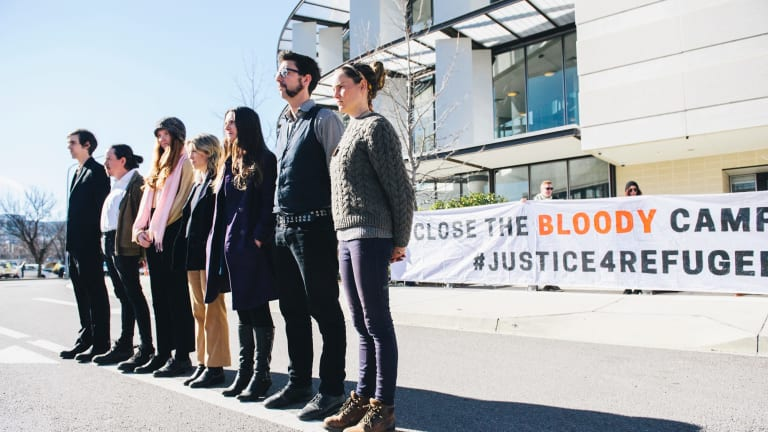 Pro-refugee protesters who super glued themselves to the railing of Parliament in front of the building after appearing in the ACT Magistrates Court on Wednesday morning.