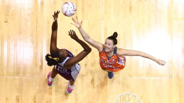 Romelda Aiken of the Firebirds and Sam Poolman of the Giants compete for the ball during their round eight Super Netball clash.