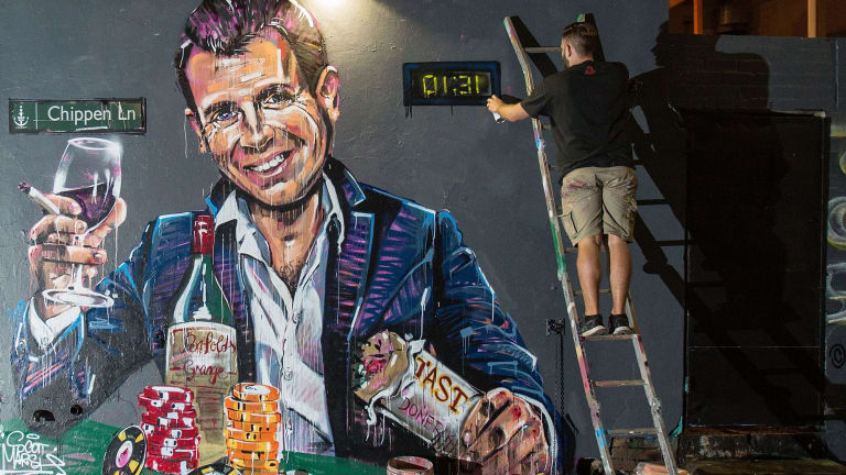 Artist Scott Marsh paints a mural of NSW Premier Mike Baird holding a kebab and glass of wine surrounded by poker chips.