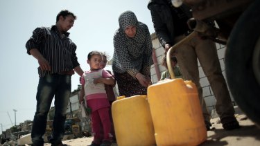 A Palestinian family fill plastic containers with drinking water they bought from a vendor in Khan Younis refugee camp, in the southern Gaza Strip.
