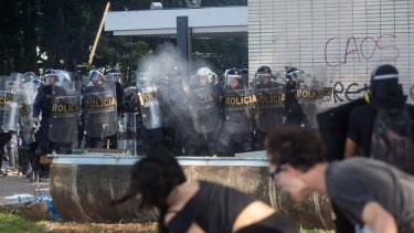Protesters against President Michel Temer throw projectiles at police in Brasilia on Wednesday.
