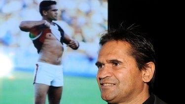 Nicky Winmar in 2013, with the famous picture of him confronting abusive Collingwood fans in 1993.