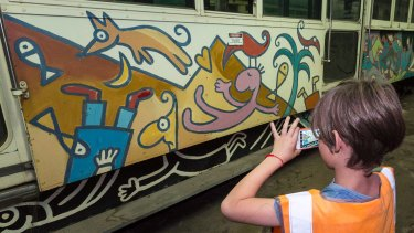 Henry Larwill takes a photo of Michael Leunig's art tram, also from 1986, now stored at the Newport Rail Yards.