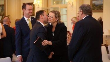 Minister for Health Sussan Ley is embraced by Assistant Treasurer Josh Frydenberg.