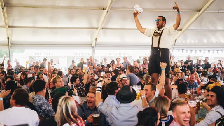 Dean Schmahl celebrates skolling a beer at Oktoberfest at the Queanbyean showground.