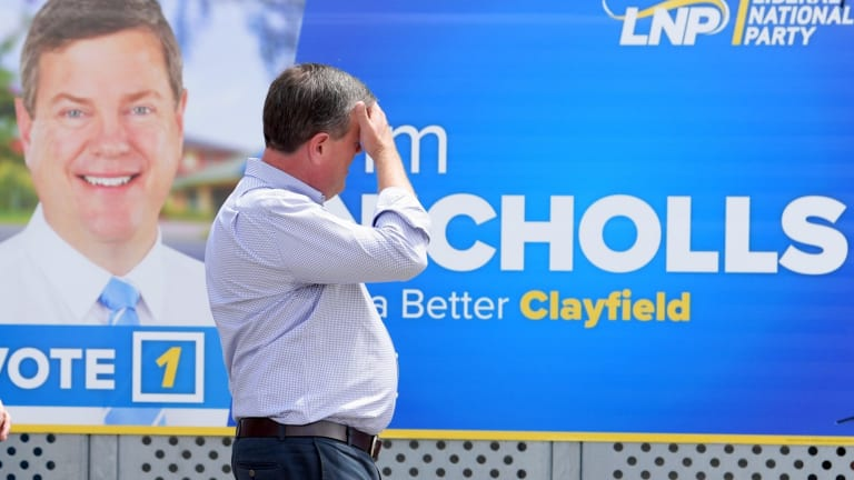 Queensland Opposition Leader Tim Nicholls walks past one of his signs on the last day of the campaign.