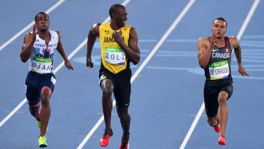 Usain Bolt smiles as he looks at Canada's Andre De Grasse during the semifinal.