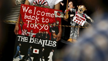 Fans hold puppets and a placard as they wait for the arrival of Paul McCartney.