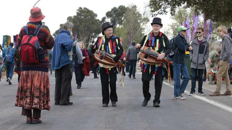 Sue and Jim Colchester of Brisbane from the Border Morris Group play their hurdy gurdy as they move through the crowd.