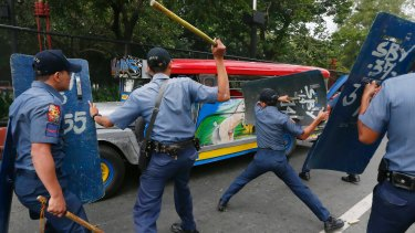 Police officers hit fleeing protesters during a violent dispersal outside the US embassy in Manila on Wednesday.