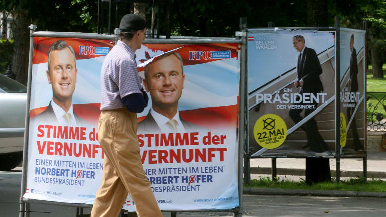 A man walks past election posters of Alexander van der Bellen, candidate for the presidential elections and former head of the Austrian Greens, right, and Norbert Hofer, of Austria's right-wing Freedom Party, left, in Vienna.