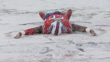 Buffalo Bills' Ryan Davis makes a snow angel on the field before the game.