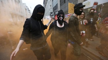 Demonstrators in masks release flares at the protest.
