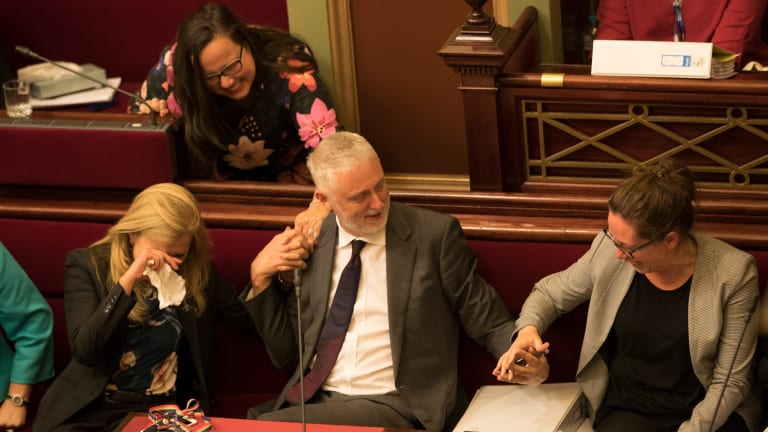 Reason Party MP Fiona Patten weeps and embraces Labor's Gavin Jennings as Jaclyn Symes takes his hand after the euthanasia bill passed Victorian Parliament's upper house.