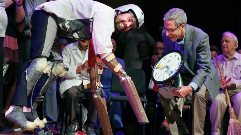 Thomas Thwaites, left, accepts the Ig Nobel prize in biology from Nobel laureate Eric Maskin while wearing his goat exoskeleton.