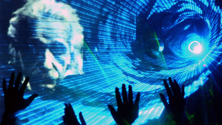 Chinese physicists wave as an image of Albert Einstein is projected during a laser show at a telecommunications company in Shanghai in 2005.