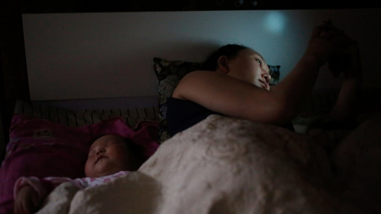 Amarzaya surfs Facebook as her young child falls asleep beside her.