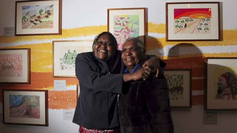 """Mother and daughter artists from Yuendumu, Tess Napaljarri Ross, right and Elisabeth Naparrurla Ross, in front of some of their work at the opening of their exhibition """"Warlpiri Drawings""""."""