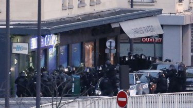 Members of the French police special forces launch the assault at a kosher grocery store in Porte de Vincennes, eastern Paris.