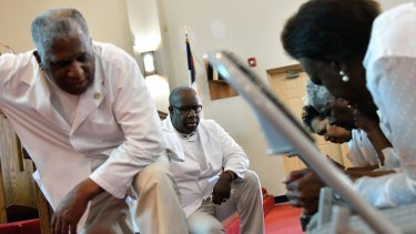 Pastor Jerry Colbert, 64, (left) listens to the prayers of members of a Singing and Praying Band group at the Hall United Methodist Church in Glen Burnie, Maryland.
