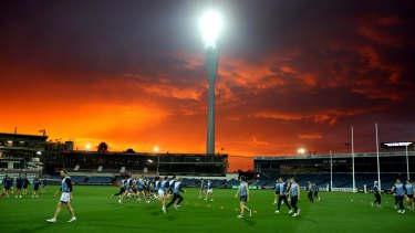 Geelong football team train under the sunset and new lights at Simonds Stadium.