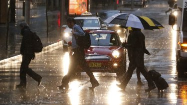 Pedestrians make their way through the wet streets of Sydney on Monday morning.