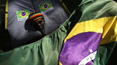 """A demonstrator peeks out from his tent, decorated with stickers that say """"Impeachment Now""""."""