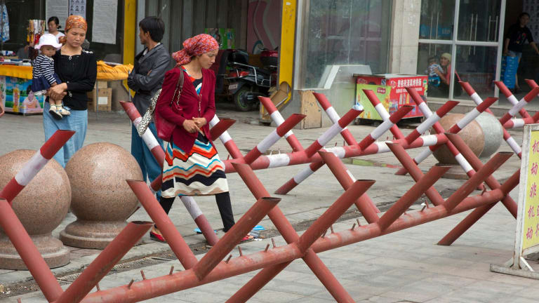 Uighur women walk past barricades set up at the entrance to a shopping district in Aksu, Xinjiang, in 2014.
