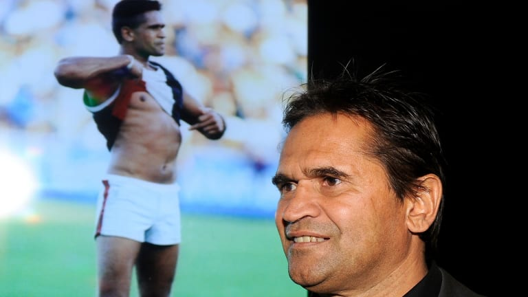 Nicky Winmar in 2013, with the famous picture of him confronting abusive Collingwood fans 20 years earlier.
