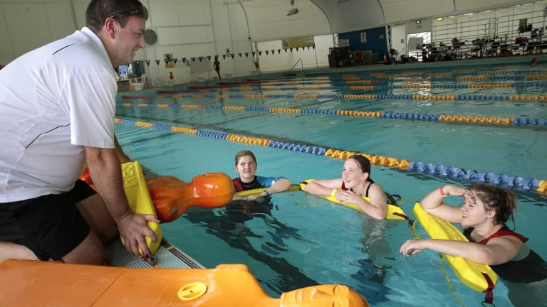 Royal Life Saving ACT training manager Ben Cuttriss instruct Calwell High School students Kirralee- Rose Schofield, year 10, Nia Cavanagh, year 7, and Lauren Smith, year 10, on the manikin tow during the school's swimming carnival at the Canberra Olympic Pool.