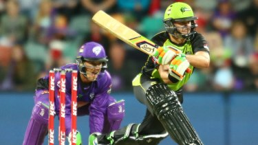 Mike Hussey of the Thunder bats as wicketkeeper Tim Paine of the Hurricanes looks on.