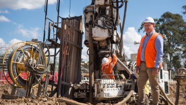 Fairwater construction manager Adam Chymiak with the rig that drills the geothermal pipelines.
