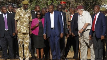 Kenya's President Uhuru Kenyatta, centre, looks on as 15 tonnes of ivory confiscated from smugglers and poachers is burnt in Nairobi National Park.